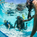 Underwater photographer - Scuba diving lesson in the resort pool. Padi course.