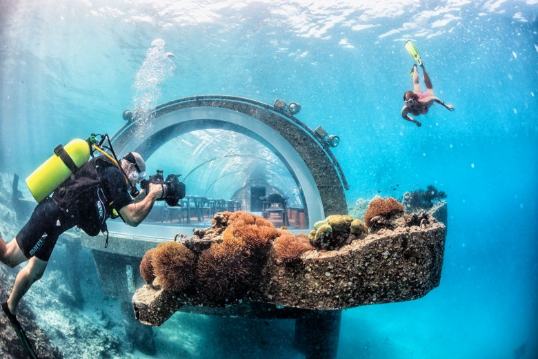 Underwater photographer - Outside of the world's largest all-glass undersea restaurant located at Hurawalhi Island Resort in the Maldives.